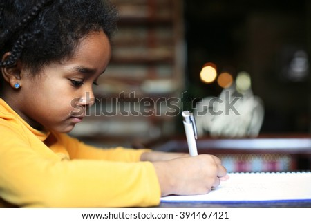 Profile of little African girl writing  in classroom.  - stock photo