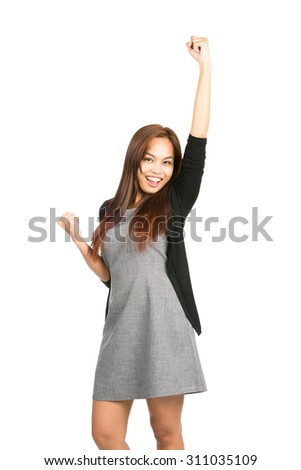 Profile of lovely Asian female in gray dress black sweater pumping fist in the air, arm raised, celebrating success, winning or achieving goal. Thai national of Chinese origin