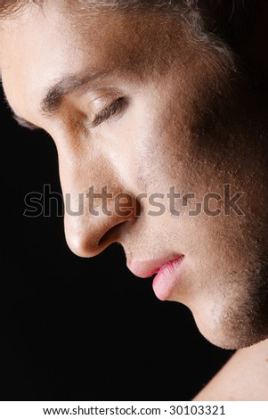 Profile of man with closed eyes closeup photo over dark background