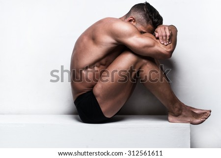 Profile of Muscular Man Wearing Black Boxer Briefs Sitting with Head Resting on Folded Arms and Leaning on Knees While Sitting on Bench in Studio with White Background and Copy Space