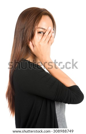 Profile of playful Asian woman in casual clothes, dress sweater, covering face with hand, eye peeking through split finger showing shy, curious, fearful emotions. Thai national of Chinese origin