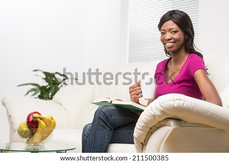 profile of relaxed young woman reading book. beautiful girl sitting on sofa at home indoor and smiling - stock photo