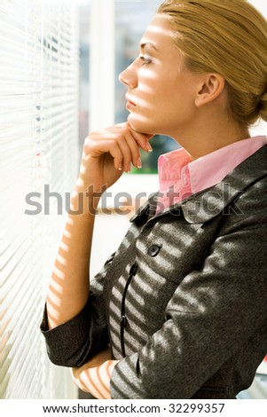 Profile of serious woman looking through venetian blind and thinking about something - stock photo
