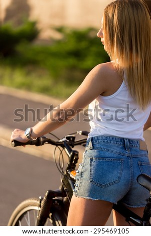 Profile of sexy sporty beautiful young woman on bike on the street on sunny summer day - stock photo