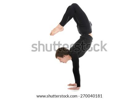 Profile of sporty yogi male doing fitness exercises, yoga asana Scorpion Pose Vrischikasana 2, handstand, inverted backbend pose - stock photo