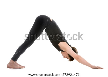 Profile of sporty young man working out, standing in yoga downward facing dog pose, adho mukha svanasana, asana from Surya Namaskar sequence, Sun Salutation complex - stock photo