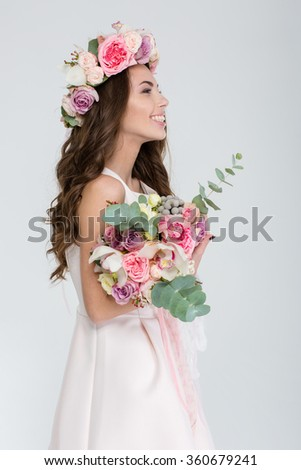Profile of tender cheerful young woman in flower wreath and wedding dress standing and holding beautiful bouquet over white background - stock photo