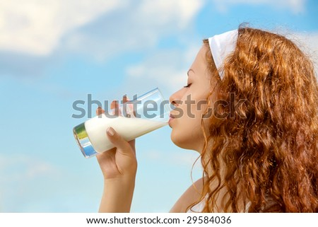 Profile of the beautiful girl drinking milk against the sky - stock photo