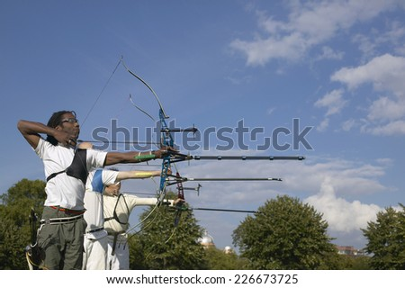 Profile of three men in a row aiming their bows in an archery contest - stock photo