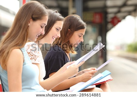 Profile of three students studying and learning reading notes in a train station - stock photo