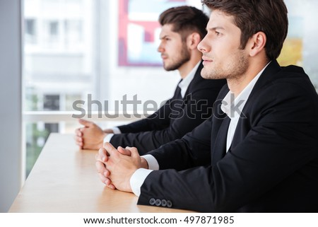 Profile of two confident young businessmen sitting in office