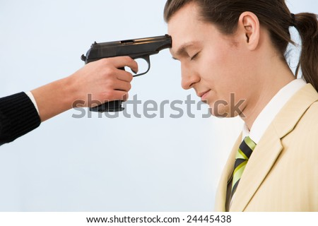 Profile of very sad businessman with gun at his forehead held by woman - stock photo