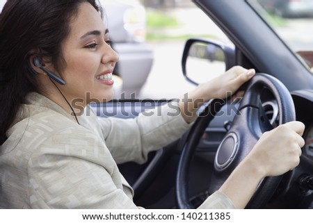 Profile of woman driving car with headset