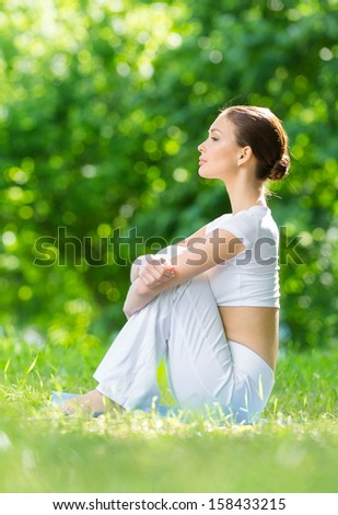 Profile of woman sitting on mat in park after exercising. Concept of healthy lifestyle and relaxation