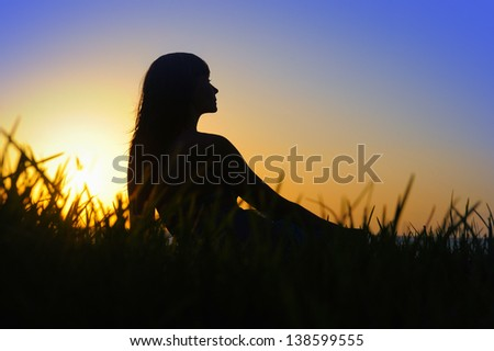 Profile of woman sitting on the grass near the sea at sunset - stock photo