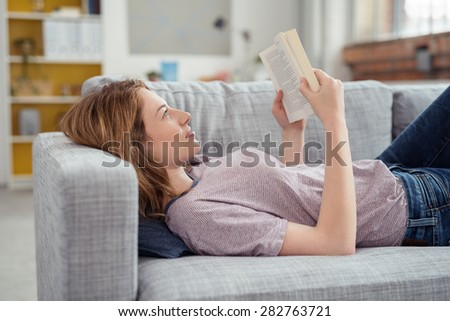Profile of Young Brunette Woman Relaxing on Sofa and Reading Novel Book at Home - stock photo