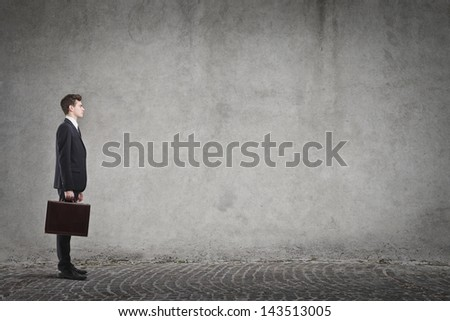 profile of young businessman with briefcase on gray background - stock photo