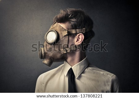 profile of young businessman with gas mask - stock photo