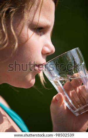 Profile of young girl holding glass of water - stock photo