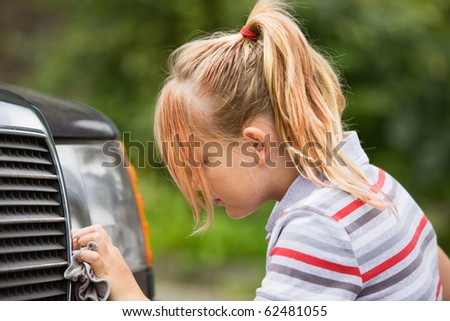 Profile of young girl washing car - stock photo