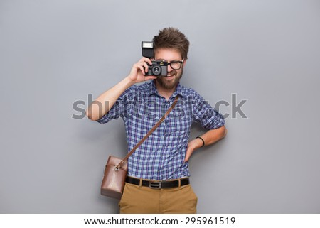 Profile of young man traveller with camera. Man in navy blue shirt making photos isolated on grey background. - stock photo