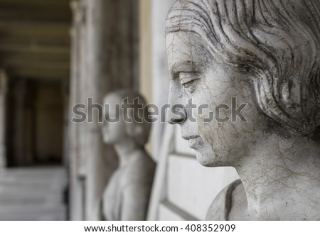 Profile of young sad woman, In the background another statue of a woman and the hall of the museum.