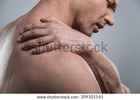 profile of young shirtless man with shoulder pain. young man standing on grey white background - stock photo