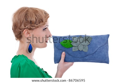 profile picture of a beautiful woman wearing nice colorful earrings and presenting a blue leather purse - stock photo