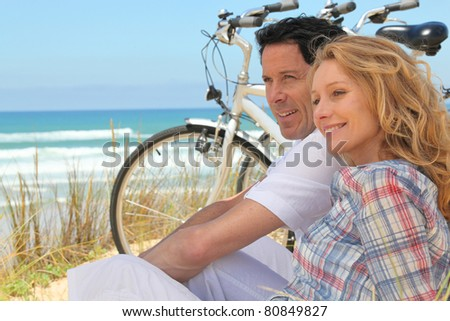 Profile picture of couple sat next to bicycles at the beach - stock photo