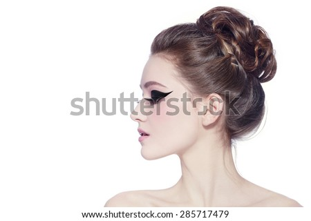 Profile poartrait of young slim beautiful girl with hair bun and fancy cat eyes over white background - stock photo