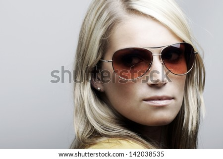 Profile portrait of a beautiful Caucasian female model posing in sunglasses, isolated on white background. - stock photo