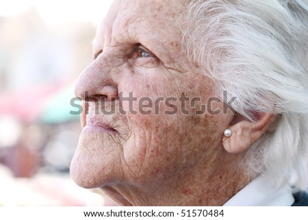 profile portrait of a beautiful octogenarian with white hair and wrinkled sun stained skin - stock photo