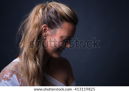Profile portrait of a blonde women . She is looking down in front of a grey background. - stock photo