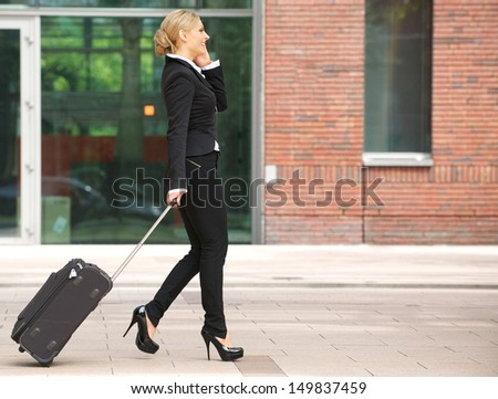 Profile portrait of a business woman walking with luggage and talking on phone - stock photo