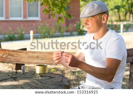 Profile portrait of a Caucasian man rolling a cigarette while sitting at a rustic wooden table outdoors, in a summer day - stock photo