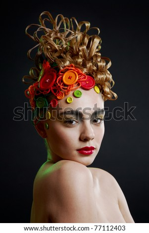 Profile portrait of a cute young woman with creativity hairstyle with colored buttons and fashion make-up - stock photo