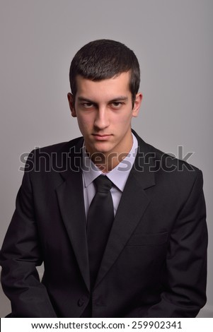 Profile portrait of a fashion young man in black suit posing in studio - stock photo