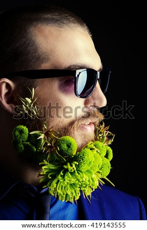Profile portrait of a handsome man in sunglasses and with a beard of green flowers. Men's beauty. Barbershop. - stock photo