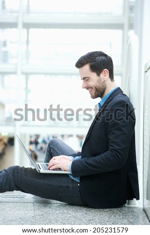Profile portrait of a handsome young man browsing the internet on laptop - stock photo