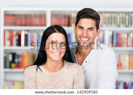 Profile portrait of a happy and cheerful couple in front of the bookshelf. - stock photo