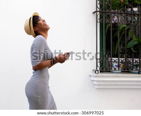 Profile portrait of a laughing young woman walking with mobile phone - stock photo