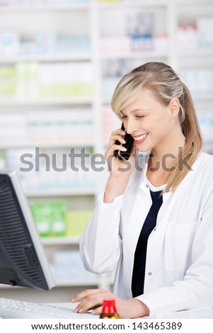 Profile portrait of a smiling attractive female pharmacist talking at the phone and using a computer