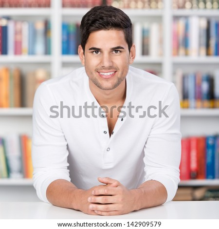 Profile portrait of a smiling young man in front of the bookshelf. - stock photo