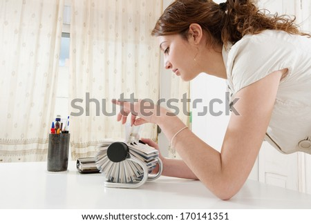 Profile portrait of a young business woman flicking through her clients contact details database on her roller deck with her fingers while at her working desk, office interior. - stock photo
