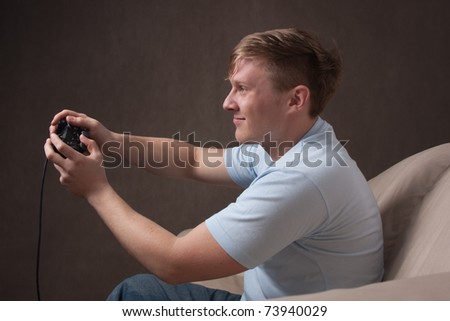 profile portrait of a young man playing video games on a gray background - stock photo