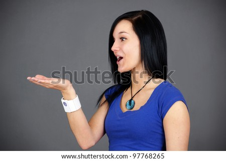 Profile portrait of an amazed young woman or student holding something up in her hand, fun advertisement. - stock photo