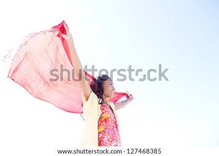 Profile portrait of an attractive african-american woman holding a red fabric sarong up in the air against a bright blue sky while on vacation, smiling. - stock photo