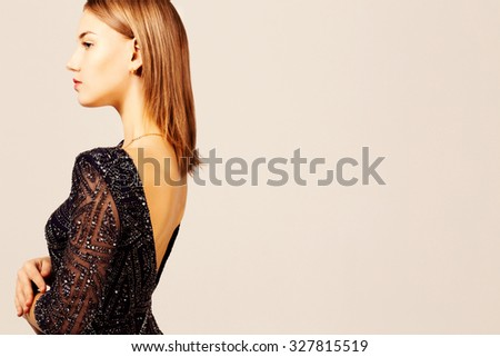 Profile portrait of an elegant  girl wearing a backless dress.  - stock photo