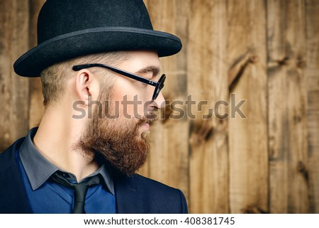 Profile portrait of an elegant man wearing suit, bowler hat and spectacles. Old style fashion.