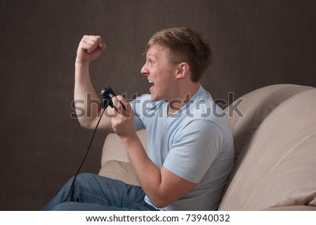 profile portrait of an excited young man playing video games on a gray background - stock photo
